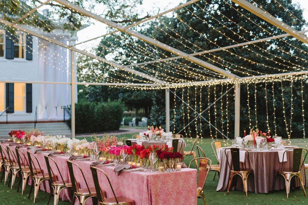 Outdoor wedding under a tent frame with twinkly lights at Woodbine Mansion